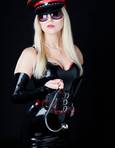 Dominatrix holding an anal hook