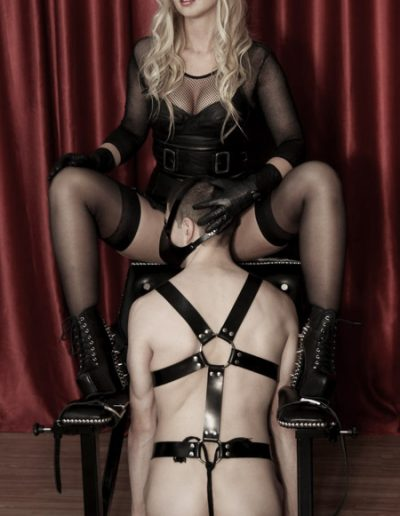 Masked blonde mistress wearing leather with slave